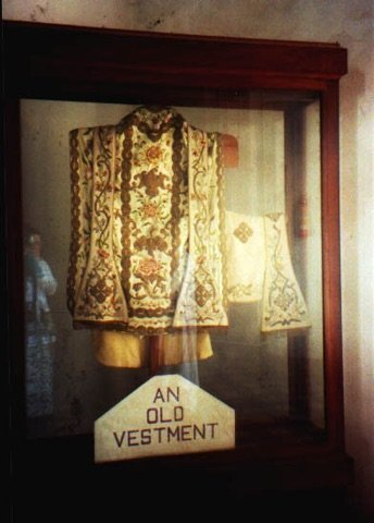 """A wooden museum cabinet containing ecclesiastical robes. A sign reads """"An old vestment""""."""