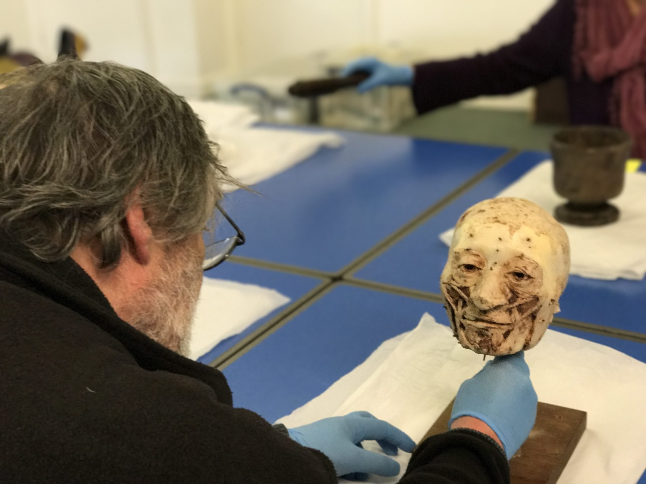 Man with greying hair wearing a blue glove beholding a wax figure of a man's face used as a mould to recreate the human face of a now deceased person in the form of an Egyptian mummy