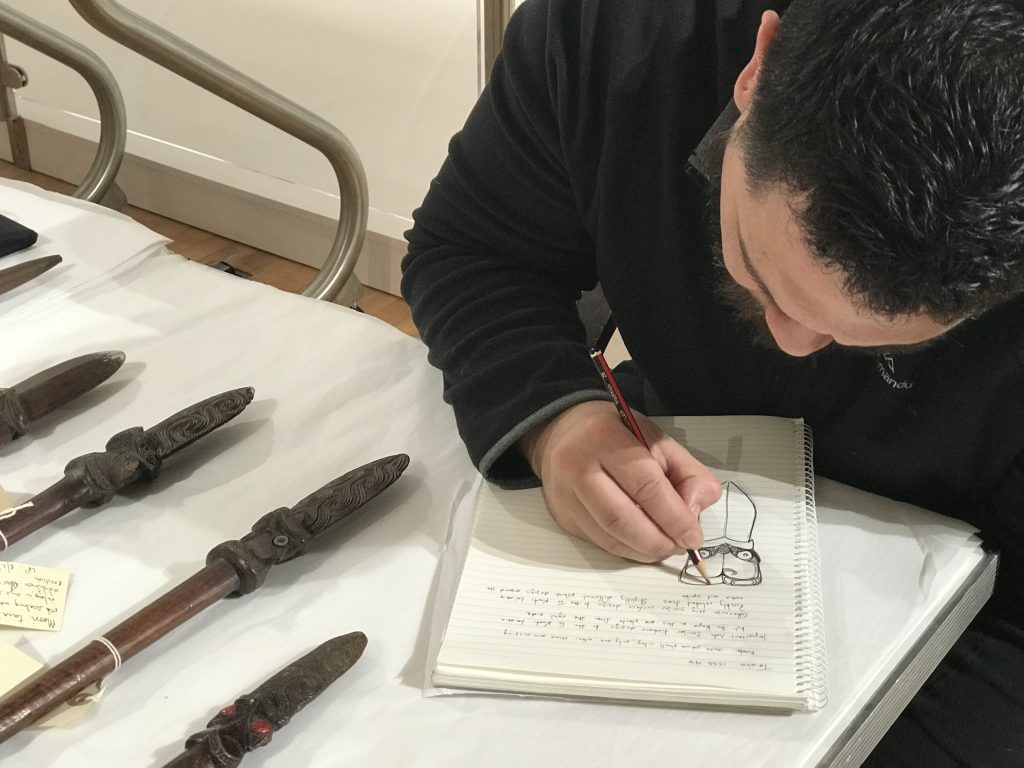 Tapunga Nepe sketching in a notebook the intricate patterns of close lines on a taiaha or combat staff used by the Māori leader Te Kooti. The head of the staff also has two red eyes made from wax and the pattern resembles a face tattoo or Tā Moko.
