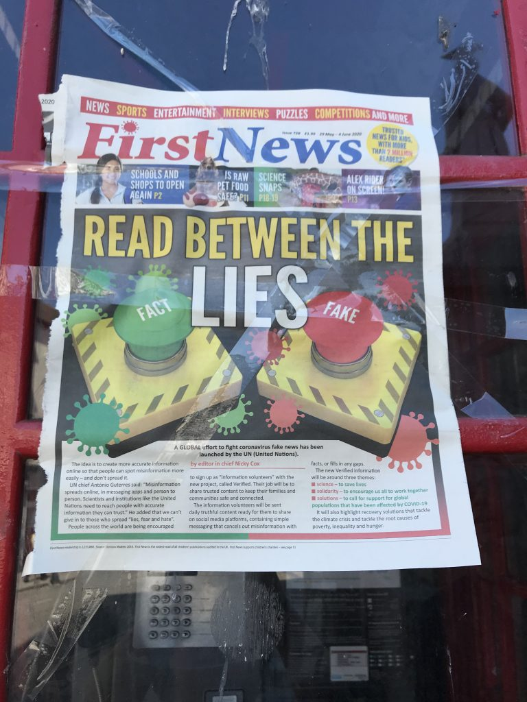 Newspaper front page. First News. Headline says Read Between the Lies with two buttons, FACT on a green knob, FAKE on a red knob.