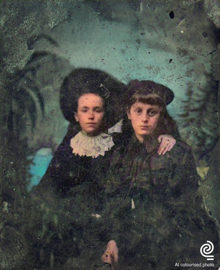 A colourised photograph from the 1860s depicting a young boy on the left wearing a big hat and a frilly ruff around his neck. He has his arm around a girl wearing a dark dress. In the damaged background a painted scene containing trees and a blue lake can be seen. All colours were computer generated in 2020.
