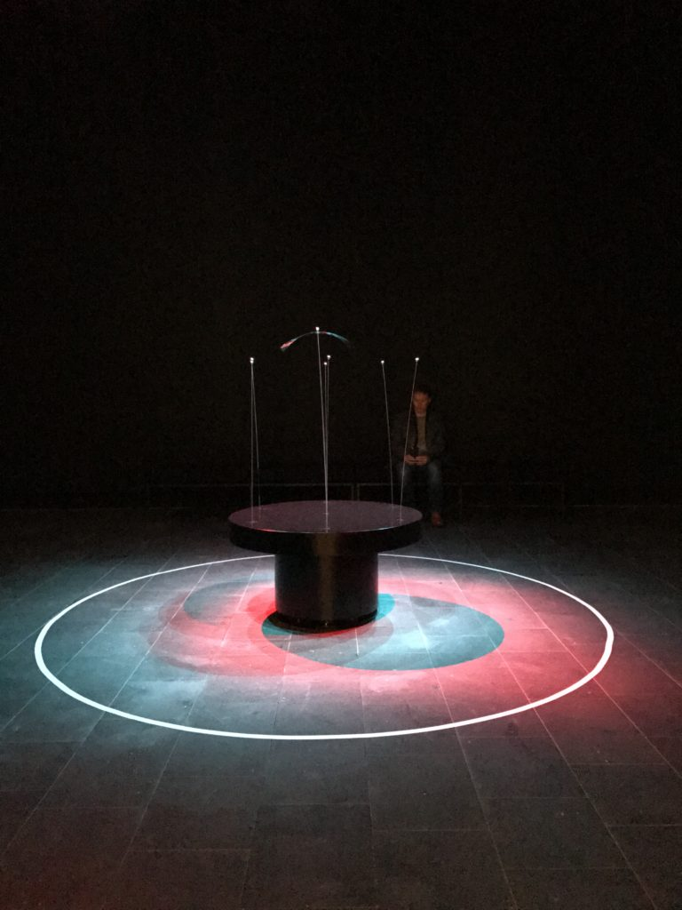 Dark black background with a central sculpture made of a set of thin and tall steel rods, flexible, with steel bearings as 'heads' the whole sculpture rotates and moves and interweaves, projected onto by blue and red lights in a circle.