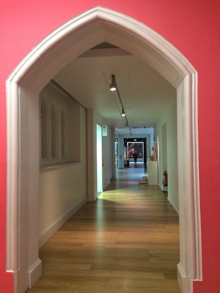Gallery corridor framed by an arch doorway picked out in white with the wall colour being lipstick pink.
