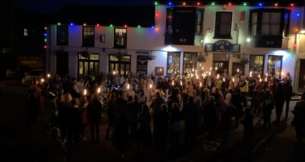 The torchlit procession on St John's Eve with the Golowan Band in their white costumes playing music by the white-painted Dock Inn. Many of the participants are holding flaming torches.
